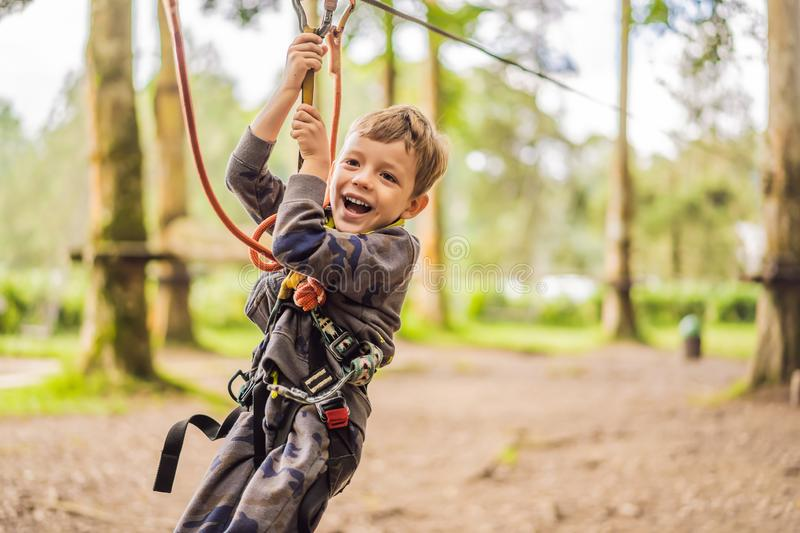 Little boy in a rope park. Active physical recreation of the child in the fresh air in the park. Training for children stock photos
