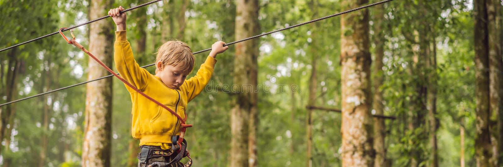 Little boy in a rope park. Active physical recreation of the child in the fresh air in the park. Training for children stock photography