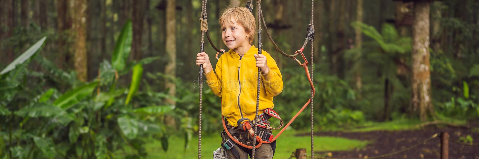 Little boy in a rope park. Active physical recreation of the child in the fresh air in the park. Training for children stock photo
