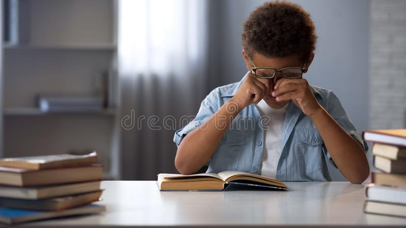 Little boy rubbing tired from active reading eyes, doing lots homework, studying. Stock photo stock image
