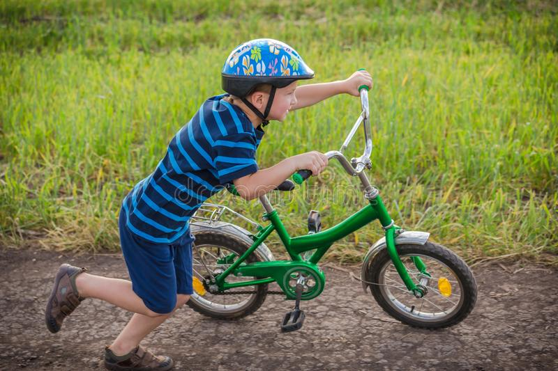 Little boy running with his bike in hands on country road stock photography