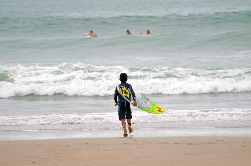 Little boy runs surfing in the ocean royalty free stock image