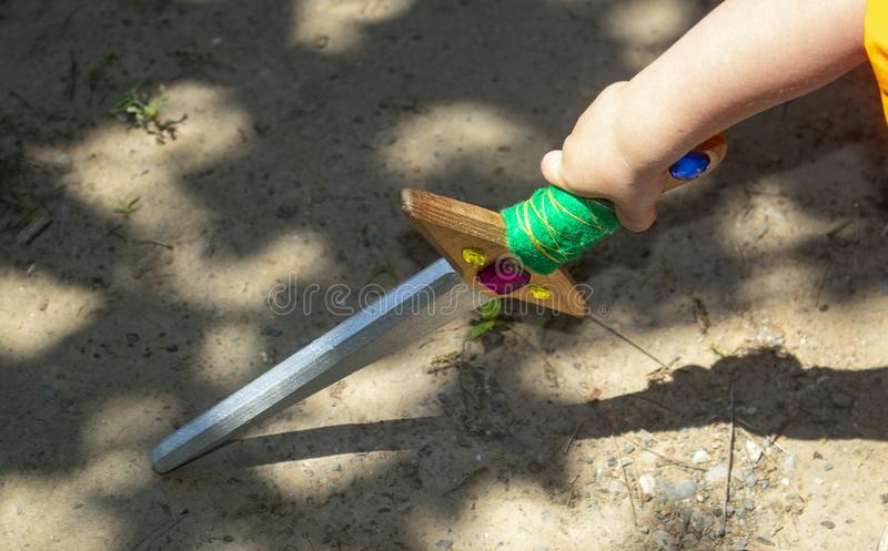 Little boy`s arm with colorful toy wooden sword touching ground with dramatic shadows royalty free stock image