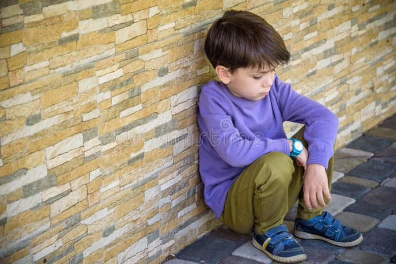 Little boy sad sitting alone at school hides his face. Isolation and bullying concept. Kid sad and unhappy, child was crying, royalty free stock photos