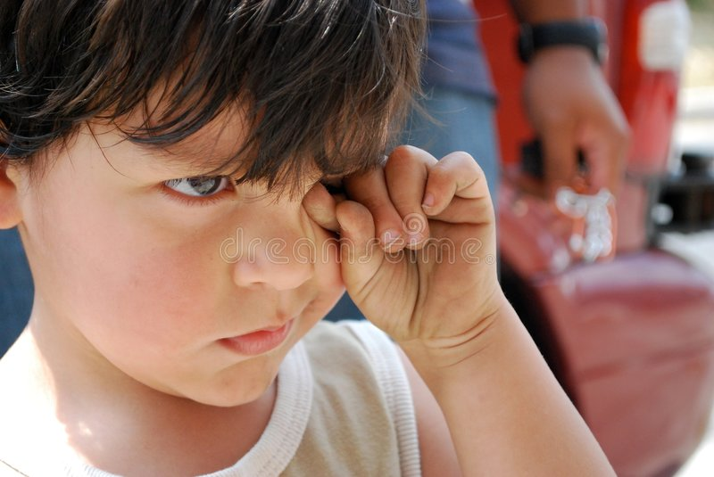 A little boy sadly rubbing his eyes stock photography