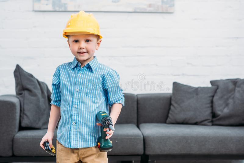 Little boy in safety helmet with toy drill pretending to royalty free stock photos