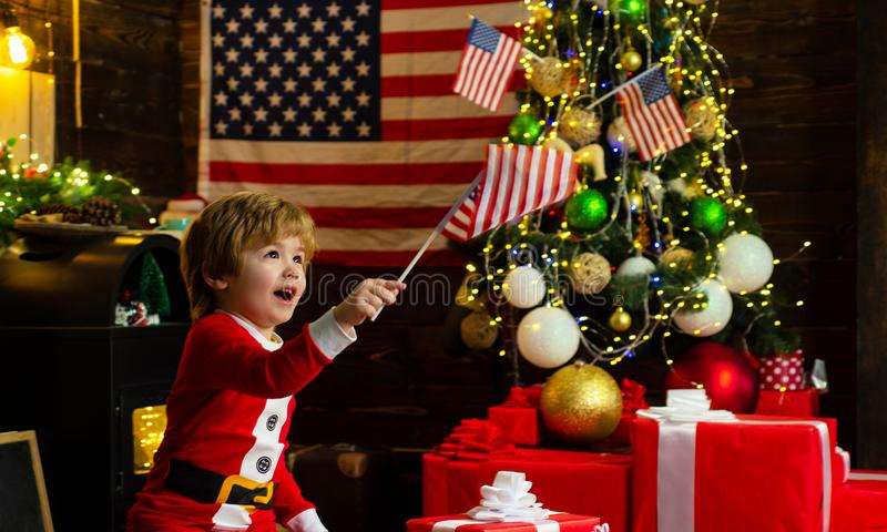 Little boy santa hat and costume having fun. American traditions concept. Cute baby toddler celebrate christmas. American child cheerful mood waving flag. Kid royalty free stock photos