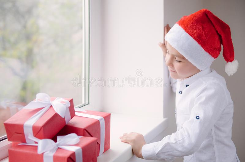 Little boy in Santa hat standing by window looking at the gifts stock photo