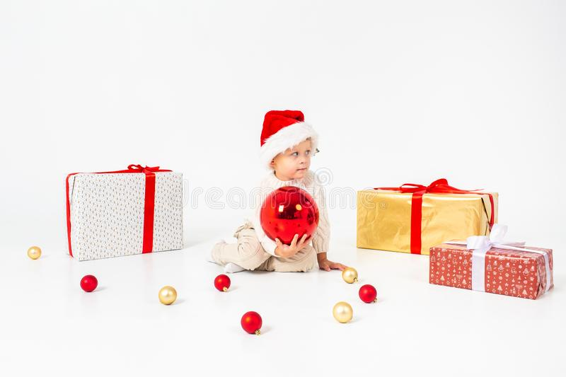 Little boy sitting between gifts and holding big red Christmas ball in hands. Isolated on white background. Holidays, christmas, royalty free stock images