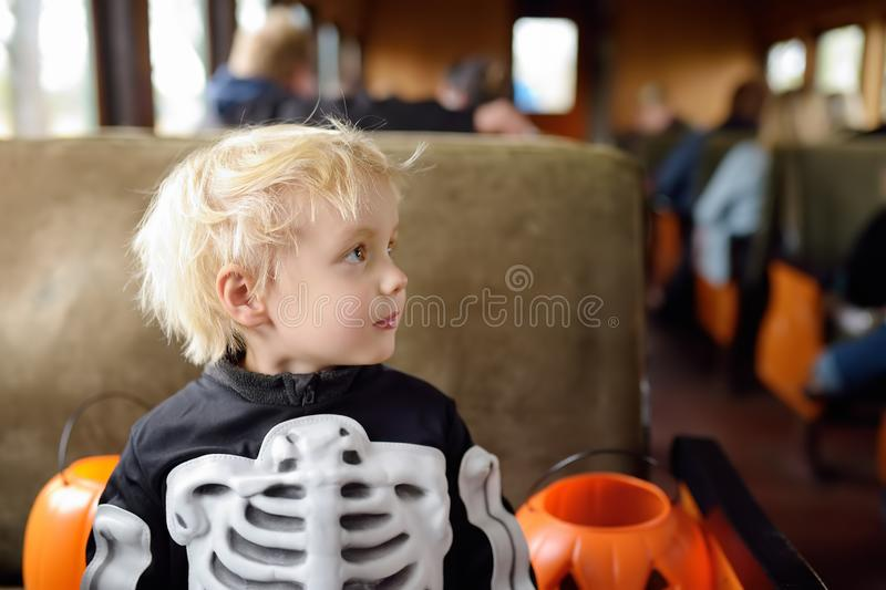 Little boy in scary costume skeleton ride in traditional train express on celebrations halloween royalty free stock photo