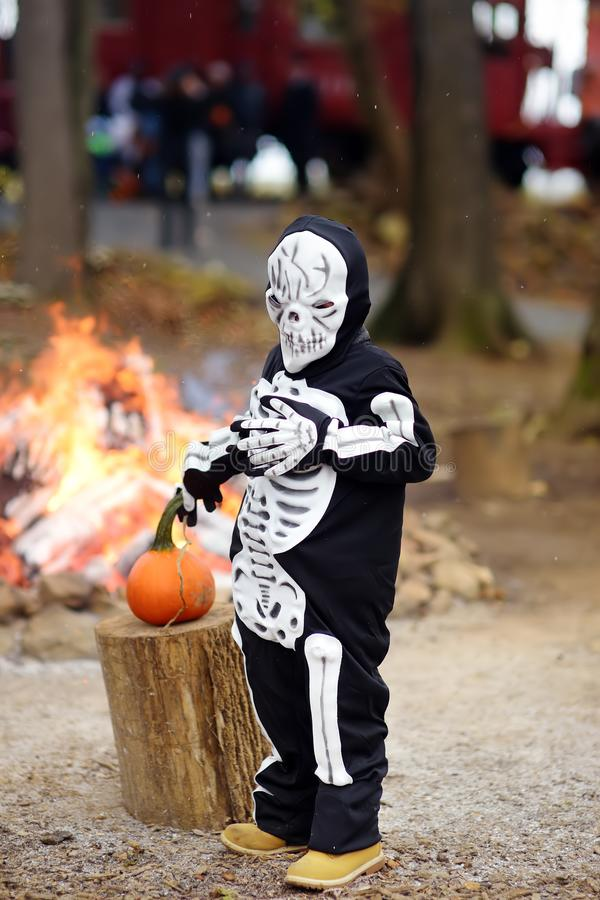 Little boy in scary skeleton costume on background of bonfire at halloween celebrations party in forest royalty free stock photos