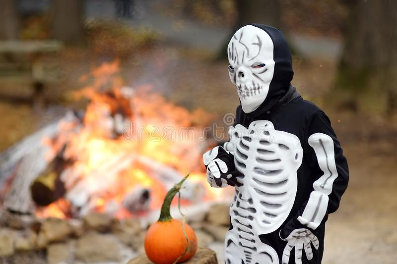 Little boy in scary skeleton costume on background of bonfire at halloween celebrations party in forest stock image