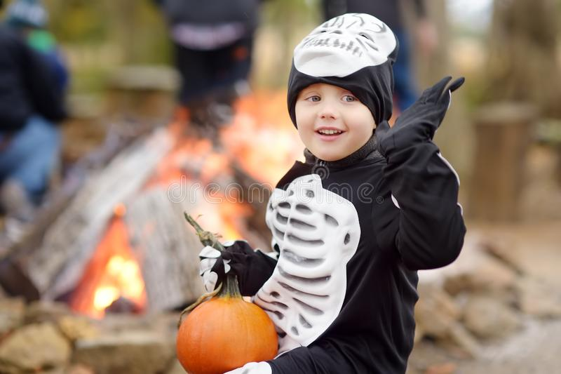 Little boy in scary skeleton costume at halloween celebrations party in forest stock image