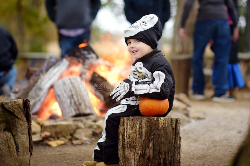 Little boy in scary skeleton costume at halloween celebrations party in forest royalty free stock image