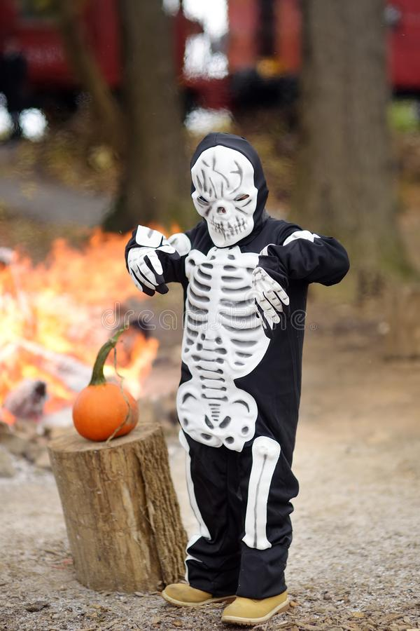 Little boy in scary skeleton costume at halloween celebrations party in forest stock photos