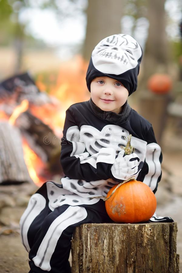 Little boy in scary skeleton costume at halloween celebrations party in forest royalty free stock images