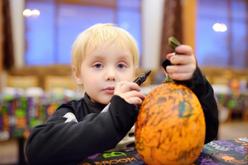 Little boy in scary skeleton costume paints pumpkin on halloween party for children stock images