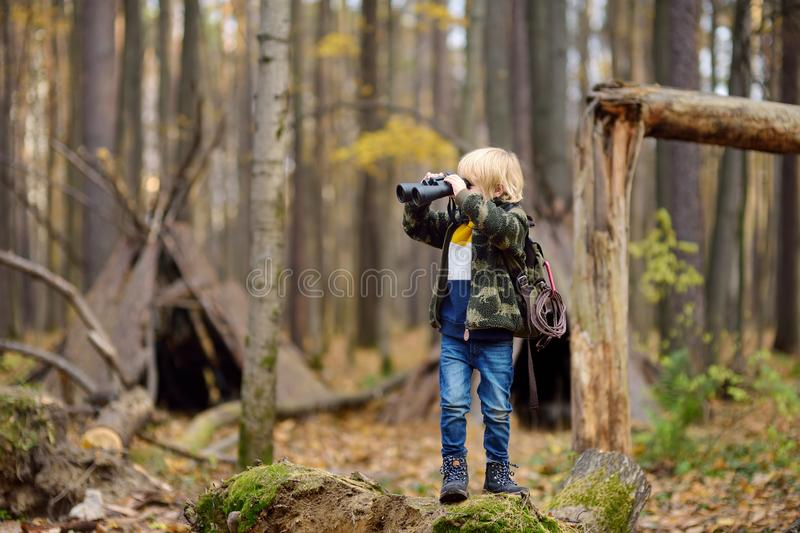 Little boy scout with binoculars during hiking in autumn forest. Child is looking through a binoculars. Behind the child is teepee royalty free stock photography