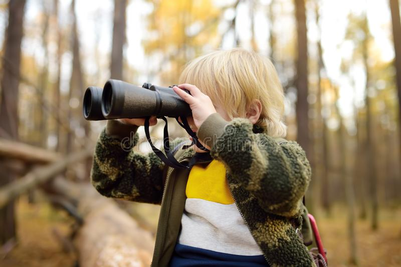 Little boy scout with binoculars during hiking in autumn forest. Child is sitting on large fallen tree and looking through a royalty free stock image