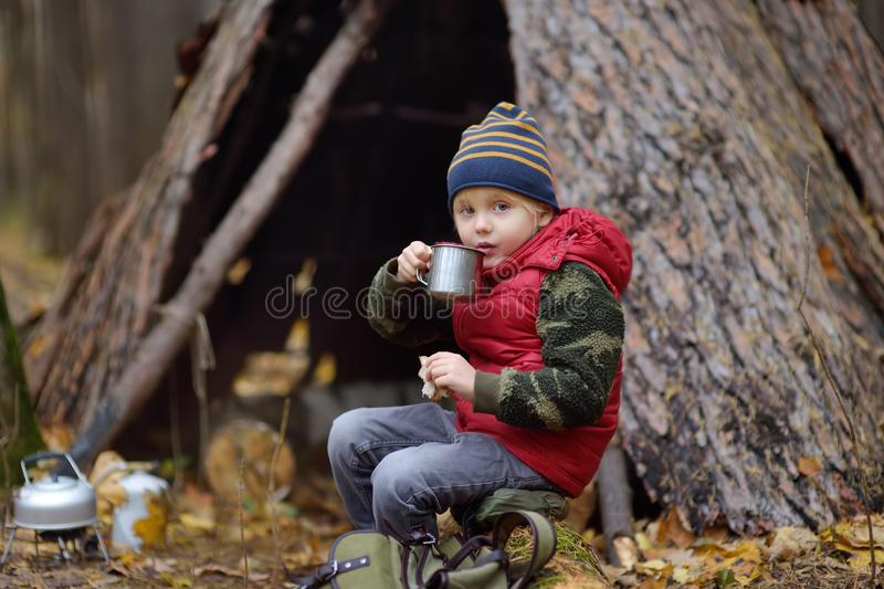 Little boy scout during hike in forest on autumn day. Child is cooking tea with help tourist gas burner and eating sandwich. royalty free stock images