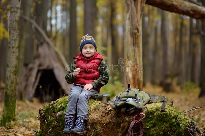 Little boy scout during hike in forest on autumn day. Child is drinking hot tea and eating sandvich. Behind the child is teepee royalty free stock photography