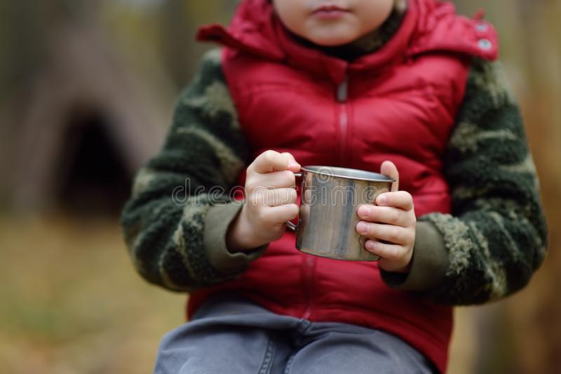 Little boy scout during hiking in autumn forest. Child is resting and drinking hot tea stock photography
