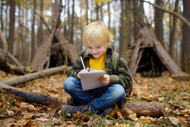 Little boy scout is orienteering in forest. Child is sitting on fallen tree and writing in the notepad. Behind the child is teepee stock images