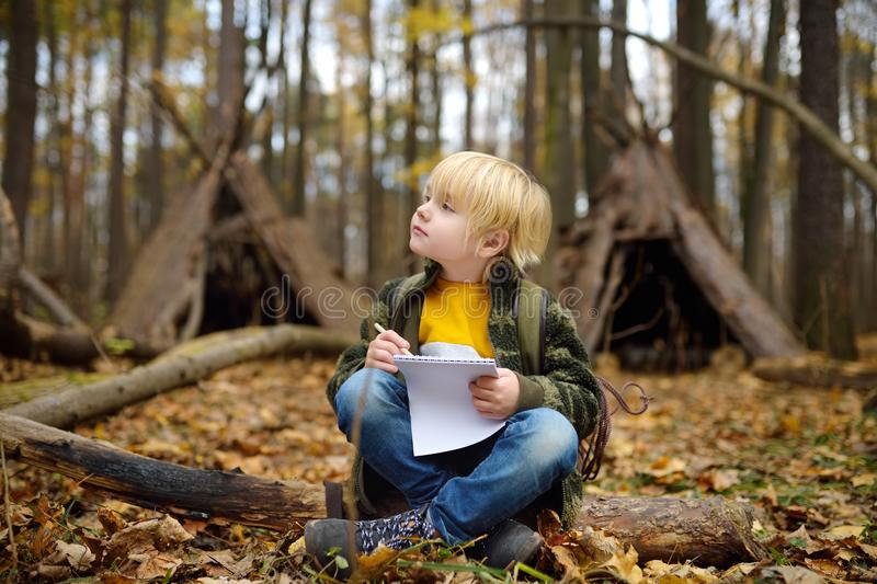 Little boy scout is orienteering in forest. Child is sitting on fallen tree and writing in the notepad. Behind the child is teepee stock image