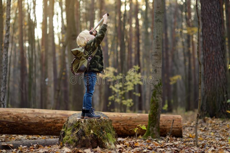 Little boy scout with spyglass during hiking in autumn forest. Child is looking through a spyglass royalty free stock image