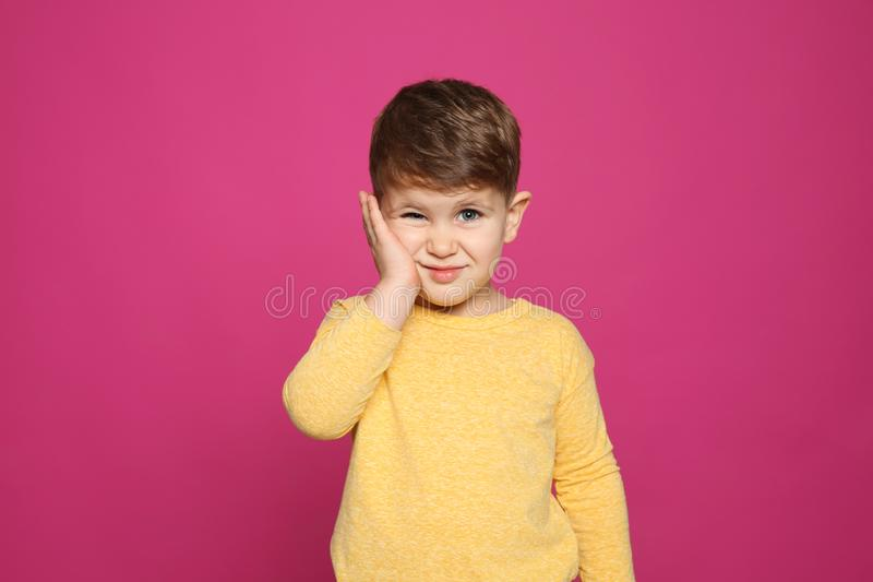 Little boy scratching face on color background. Annoying itch royalty free stock photography