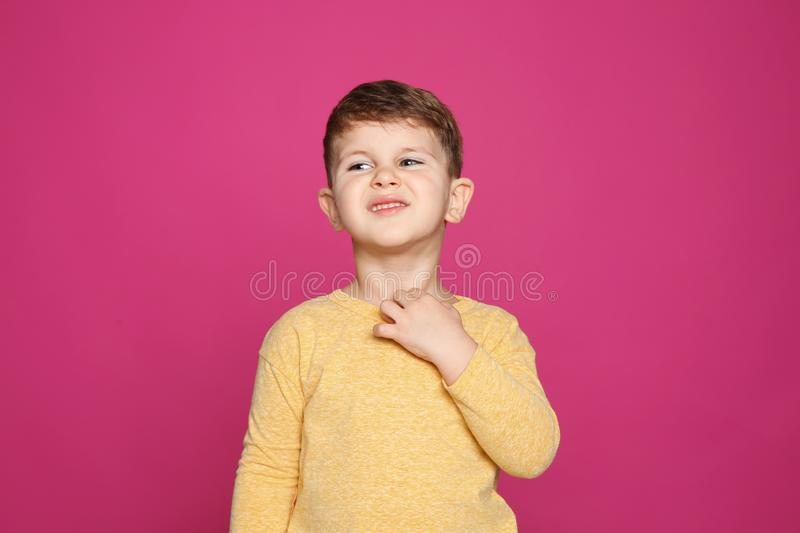 Little boy scratching neck on color background. Annoying itch stock photo