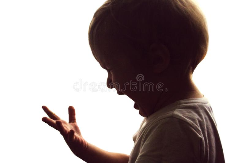 The little boy screams and cries. stock images