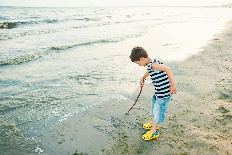 The little boy by the sea throws stones in water. sunset. Happy childhood. Summer vacation at sea or ocean, activity, adorable, baby, beach, beautiful, blue royalty free stock images