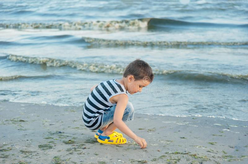 The little boy by the sea throws stones in water. sunset. Happy childhood. Summer vacation at sea or ocean, activity, adorable, baby, beach, beautiful, blue royalty free stock photo