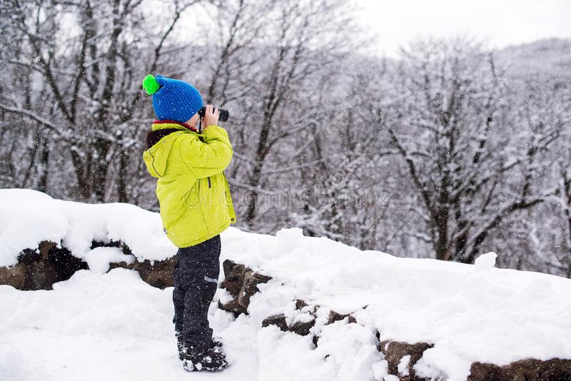 Little boy searching Santa claus house in a mountains. Kid boy using binoculars and having fun on winter walk in forest. Christmas royalty free stock image