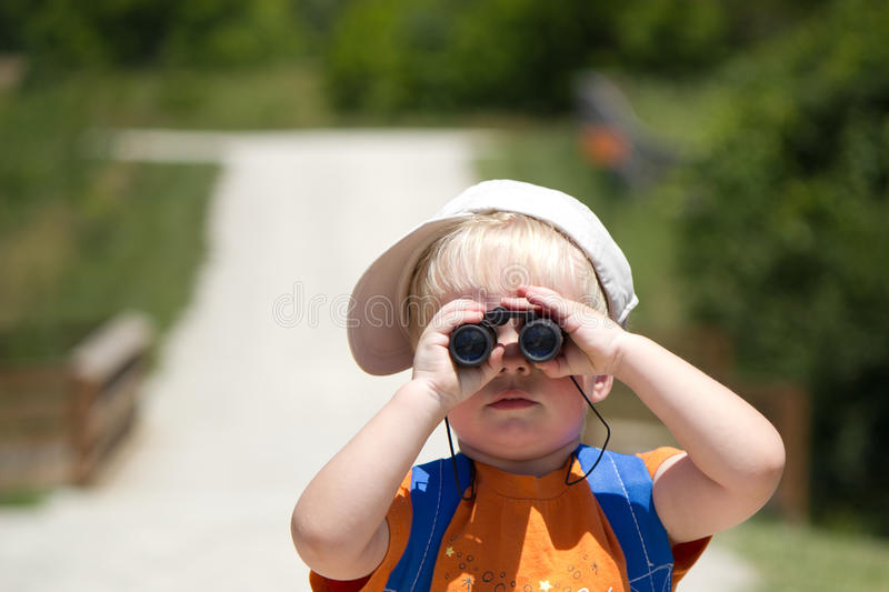 Little boy searching, searches with binoculars. Little boy looks through binoculars, searches, searching royalty free stock photo
