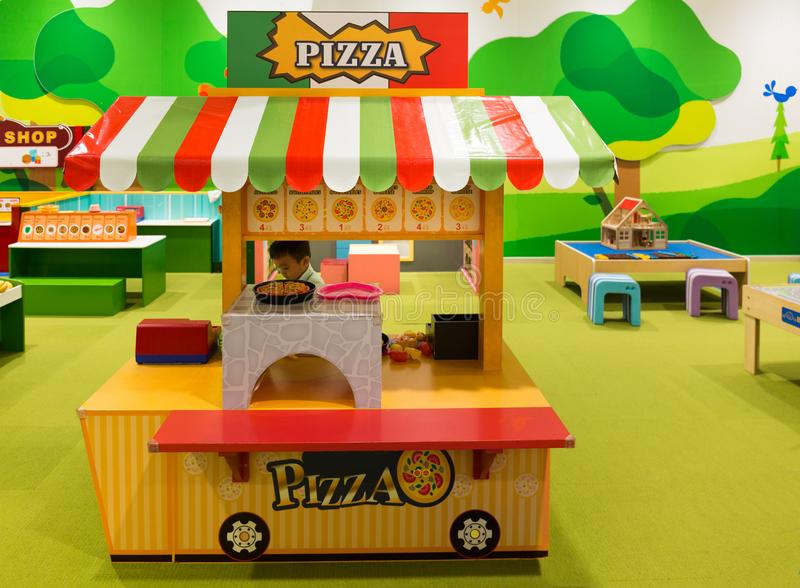 Little Boy Selling Toy Pizza in a Pizzeria at the Children Playground royalty free stock images