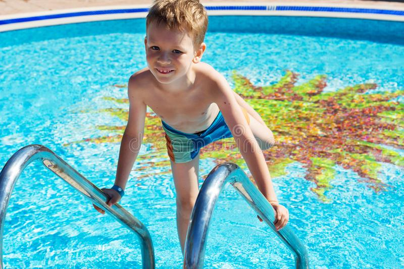 Happy kid playing in blue water of swimming pool. Little boy learning to swim. Summer vacations concept. Cute boy swimming in poo. Little boy in hat, shirt and royalty free stock photo