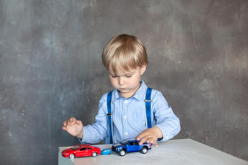 A little boy in a shirt with suspenders plays with toy multi colored toy cars. Preschool boy playing with toy car on a table at ho. A little boy in a shirt with stock photos