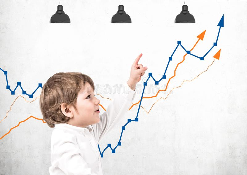 Little boy showing growing graph. Side view of adorable little boy in white shirt pointing at growing graphs drawn on concrete wall. Future of business and royalty free stock image
