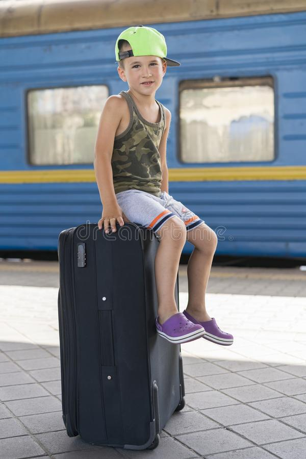 A little boy siting on a big black suitcase at the station. Concept of travel and adventure. vertical photo royalty free stock image