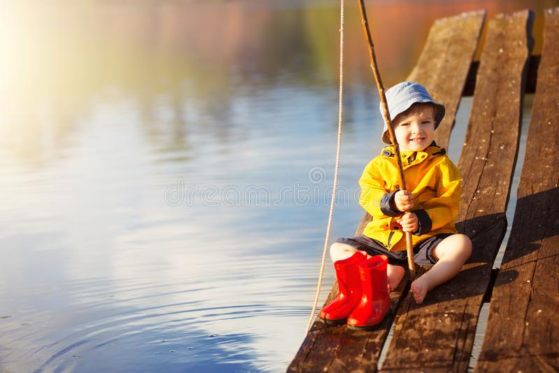 Little boy siting on wooden dock and fishing at sunset royalty free stock photo