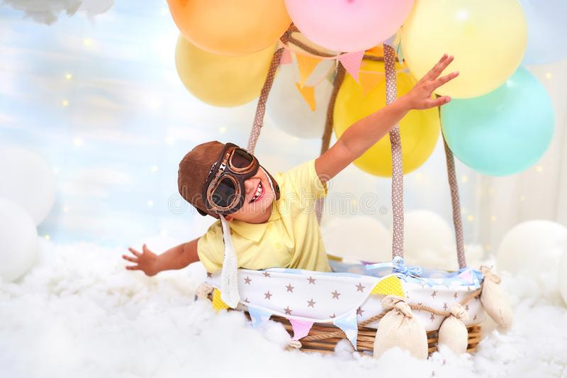 A little boy sits in a balloon basket in the clouds, pretending to travel and fly with an Aviator hat for a concept of creativity stock photography
