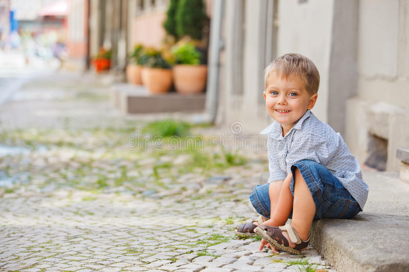 Little Boy Sits On The Doorstep On A City Street Royalty Free Stock Photography