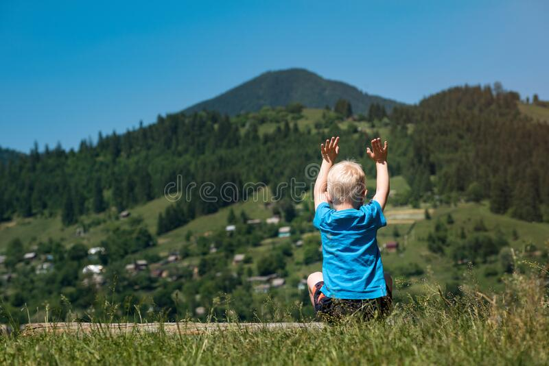 Little boy sits on mountains background with hands raised up. Back view stock photography