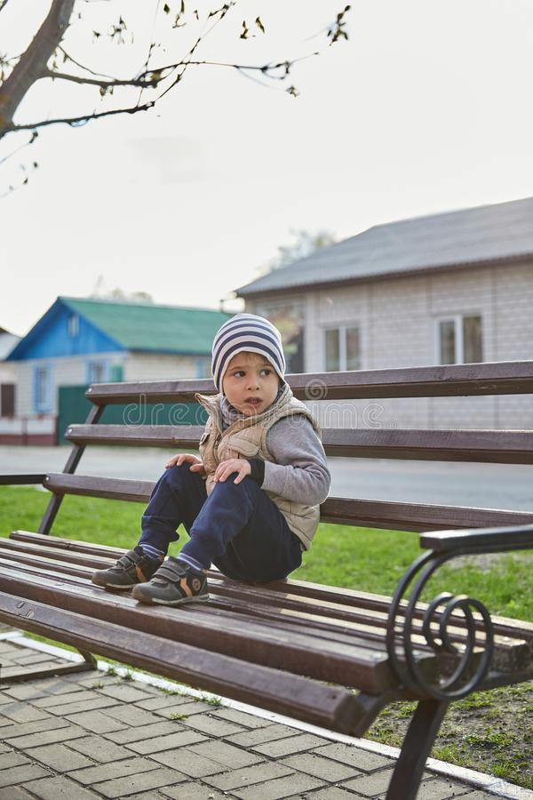 Little boy sitting on a bench. baby alone in the city royalty free stock images
