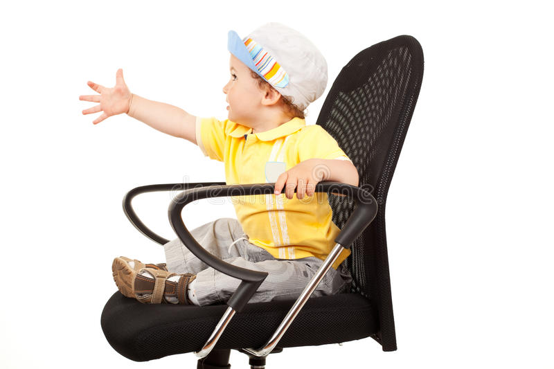 Little boy sitting on a chair stock photos