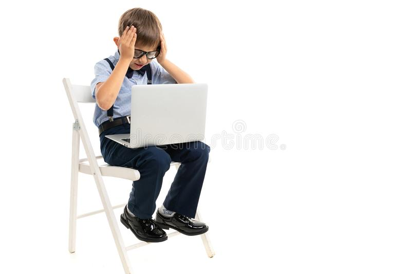 Little boy sitting on a chair and holding his head while holding a laptop on his lap on a white background.  vector illustration