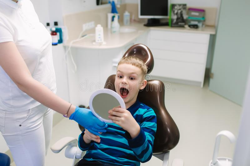 Little boy sitting in dantist chair with mirror. Male patient look at his teeth royalty free stock images