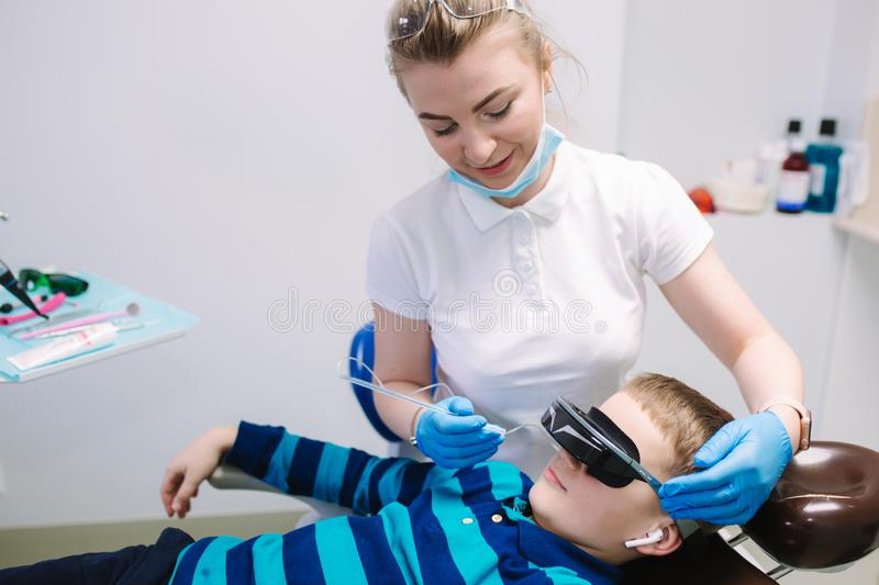Little boy sitting in dentist in vr glasses and wireless headphones while dentist make x-ray of teeth. male patient stock photos